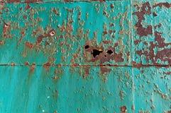 La rouille a formé des trous dans une porte en métal photographie stock