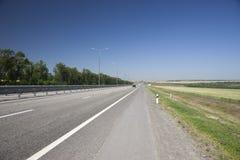 La route à la gauche de la barrière In un fond brouillé, voitures viennent photos stock