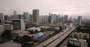 La route achemine des banlieusards le long des édifices hauts latéraux à Miami la Floride clips vidéos