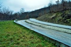 La route allument une montagne nuageuse Image stock