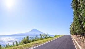 La route asphaltée aux Açores va le long des rivages herbeux de l'Océan Atlantique, sur un fond d'un volcan éteint Image libre de droits