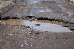 La route asphaltée par mauvais Grand nid de poule rempli avec de l'eau Assiette de la route détruite dangereuse photos stock