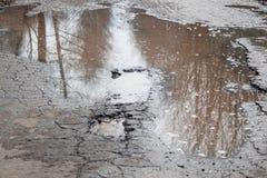 La route asphaltée par mauvais Grand nid de poule rempli avec de l'eau Assiette de la route détruite dangereuse photo libre de droits