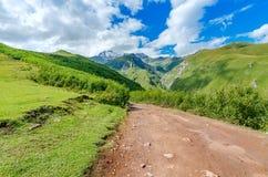 La route avec le pneu dépiste mener aux montagnes et photos libres de droits