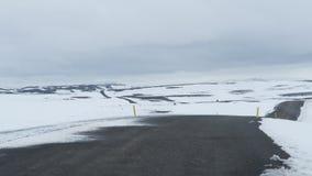 La route a courbé sans fin dans les champs neigeux Photos stock