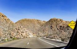 La route d'enroulement sinueuse passant par la roche a couvert des montagnes Images stock