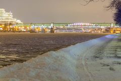 La route dans les dérives de neige près de la rivière en parc le soir image stock