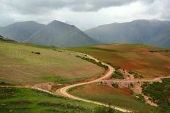 La route de campagne incurvée par S a coupé profondément par le secteur d'agriculture en vallée des montagnes des Andes, Cusco, P photo libre de droits