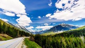 La route de lac Duffey, la route 99, en tant qu'elle s'enroule par la chaîne de montagne couverte par neige de côte Images stock