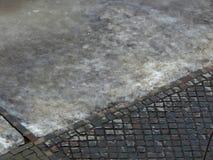 La route de pavé rond et de l'autre côté là est l'eau et glace Photos stock