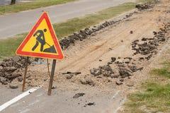 La route est en construction avec un panneau d'avertissement et un nouvel asphalte étendus Images libres de droits