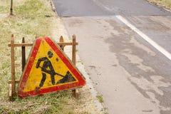 La route est en construction avec un panneau d'avertissement et un nouvel asphalte étendus Photos stock