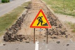 La route est en construction avec un panneau d'avertissement et un nouvel asphalte étendus Photo stock