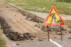 La route est en construction avec un panneau d'avertissement et un nouvel asphalte étendus Photo libre de droits