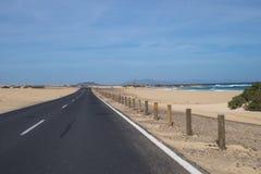 La route goudronnée par les dunes de sable Photographie stock