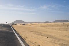 La route goudronnée par les dunes de sable Photographie stock libre de droits