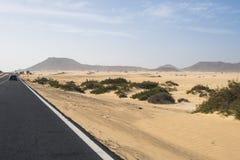 La route goudronnée par les dunes de sable Photos libres de droits