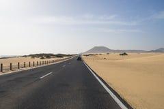 La route goudronnée par les dunes de sable Images libres de droits