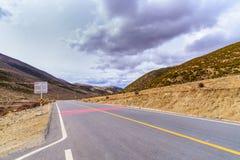 La route incurvée vide de manière élevée de route goudronnée opacifie, ciel et montagne photo libre de droits