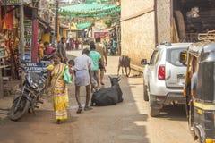 La route indienne dans la ville et les piétons dévient la vache se trouvant sur la route images libres de droits
