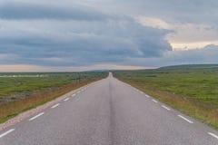 La route m'étire dans la distance sur un fond de vert photos libres de droits