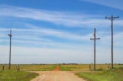 La route moins a voyagé - les routes croisées rurales avec un chemin de terre rouge menant en avant au-dessus de l'horizon dans l images stock