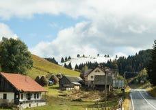 La route passant par le village au pied de la route de CarpathiThe passant par le village au pied du carpathien image libre de droits