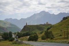 La route pavée de la Géorgie a entouré par de hautes montagnes vertes image libre de droits
