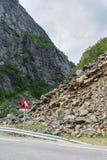 La route près de la pente de émiettage dangereuse et du panneau d'avertissement Image libre de droits