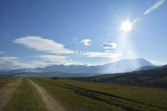 La route rurale, le ciel bleu et le soleil Photographie stock libre de droits