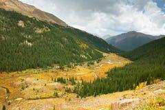La route 82 suit le long d'un courant pendant qu'elle descend du passage de l'indépendance près d'Aspen, le Colorado image stock