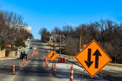 La route urbaine par un parc en construction avec quatre ruelles a réduit à deux avec au foyer signe dedans le premier plan et le images libres de droits