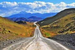 La route va aux roches noires couvertes de neige Photos libres de droits