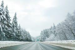 La route vide avec le niveau élevé de neige a couvert le paysage dans des mers d'hiver Photos libres de droits