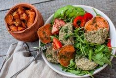 La rucola, lenticchia del vegano ha fritto le cotolette, patata dolce al forno Fotografie Stock