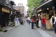 La rue antique de personnes de touristes marchant des bâtiments en bois fait des emplettes, Takayama, Japon Image libre de droits