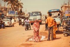La rue d'une ville indienne avec des conducteurs, les passagers, les vélos et le transport trafiquent extérieur Images libres de droits
