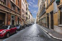 La rue italienne avec des voitures a garé sur des pavemen d'un pierre-bloc d'étroit photo stock