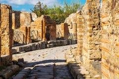La rue pavée antique est récupérée au milieu des ruines romaines à Pompeii, Italie photos libres de droits