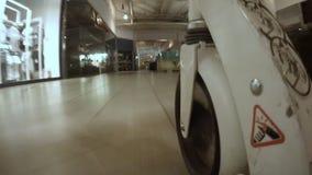 La rueda de la carretilla del supermercado de la visión inferior se mueve a lo largo de tienda almacen de video