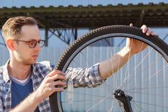La rueda de la reparación del hombre del mecánico de la bicicleta outdoor Foto de archivo libre de regalías