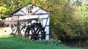 La rueda de molino de trabajo de agua que da vuelta por el poder del agua en el pequeño lago acumula escena rural del idilio metrajes