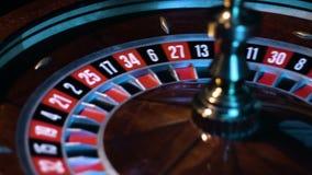 La rueda de ruleta rusa está haciendo girar con la pequeña bola blanca está circundando en la mesa de juegos en el casino almacen de video