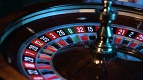 La rueda de ruleta rusa está haciendo girar en un casino y la pequeña bola blanca está mintiendo en una ranura metrajes