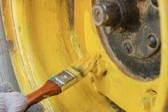 La rueda del vehículo todo terreno se pinta en amarillo con un cepillo fotos de archivo