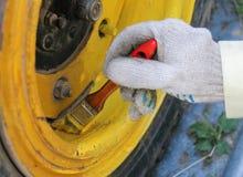 La rueda del vehículo todo terreno se pinta en amarillo con un cepillo fotografía de archivo