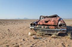 La ruina del coche clásico del salón abandonó profundamente en el desierto de Namib de Angola Imagenes de archivo