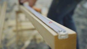 La ruleta de medición del hombre mide el haz de madera largo para la construcción almacen de video