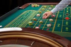 La ruleta y las pilas de juego salta en una tabla verde Fotos de archivo
