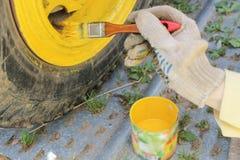 La ruota del veicolo per qualsiasi terreno è dipinta nel giallo con una spazzola immagine stock libera da diritti